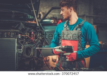 Mechanic with pneumatic tool in a workshop - stock photo