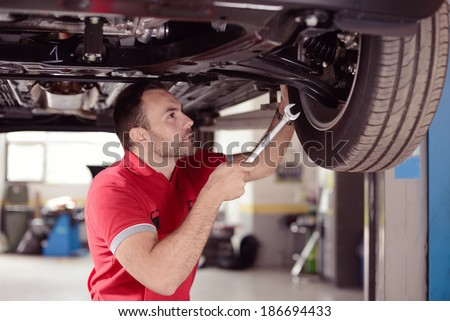 mechanic with tool checking the car - stock photo