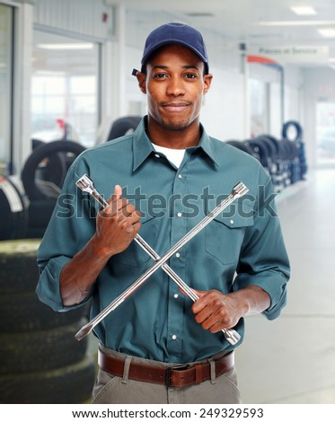 Mechanic with wrench in garage. Car repair service - stock photo