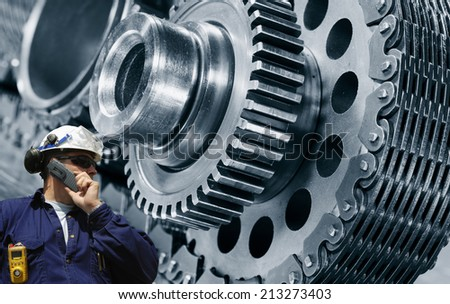 mechanic, worker with power driven cogwheels machinery, steel and metal industry - stock photo