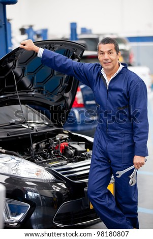 Mechanic working at the garage and fixing a car - stock photo