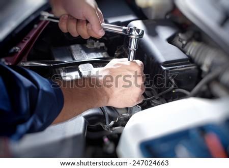 Mechanic working in auto repair garage. Car maintenance - stock photo