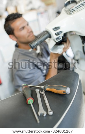 Mechanic working on scooter - stock photo