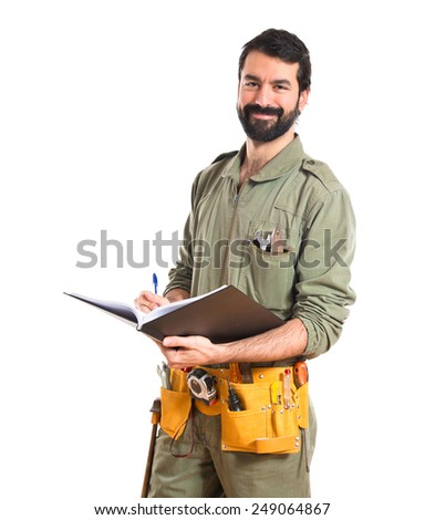 mechanic writing on book  - stock photo