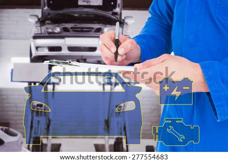 Mechanic writing on clipboard against auto repair shop - stock photo