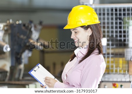 Mechanical engineer taking notes at metallurgy factory - stock photo