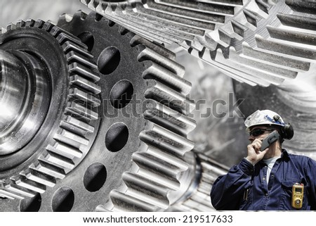 mechanical engineer, worker with giant cogwheels and gears machinery - stock photo