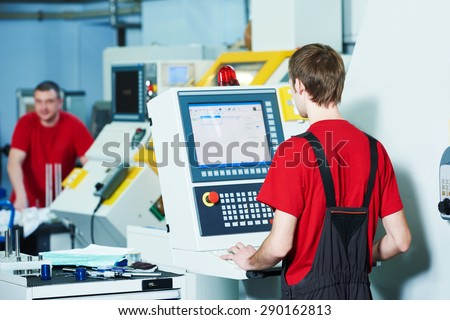 mechanical industrial worker at milling machine center in tool manufacture workshop - stock photo