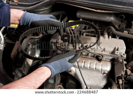 Mechanical repairs a car in the garage. - stock photo