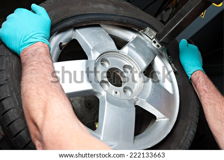 Mechanical repairs a tire in the garage. - stock photo