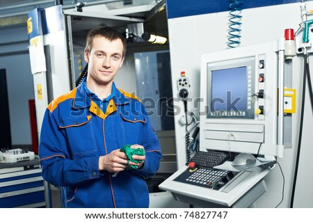 mechanical technician near cnc milling machine center at tool workshop - stock photo