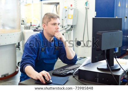 mechanical technician operative of cnc milling cutting machine working at computer at tool workshop - stock photo