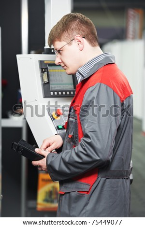 mechanical technician worker at cnc metal machining milling center in tool workshop - stock photo