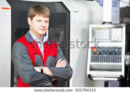 mechanical technician worker near modern cnc metal machining milling center in tool workshop - stock photo