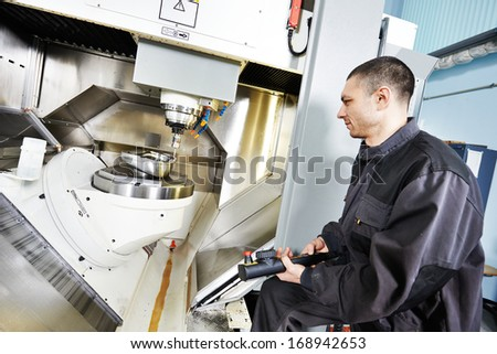 mechanical technician working at cnc milling machine center in tool workshop - stock photo