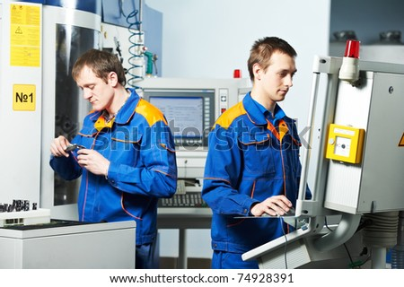 mechanical technicians working at cnc milling machine center in tool workshop - stock photo