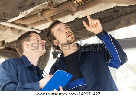 Mechanics at work. Two confident mechanics working at the work shop - stock photo