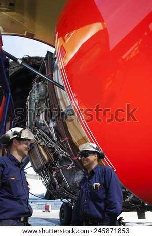 mechanics, engineers and large jumbo jet engine turbine - stock photo