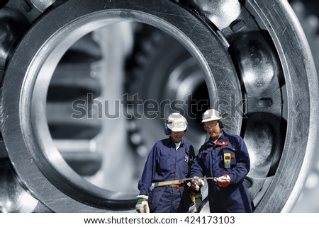 mechanics, engineers with giant steel bearings in background - stock photo