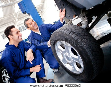 Mechanics fixing a car puncture at the garage - stock photo