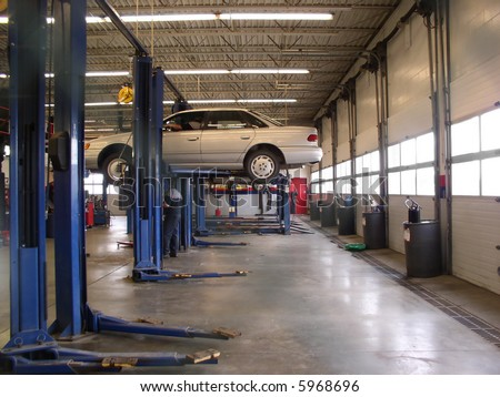 Mechanics Garage with car on hoist - stock photo