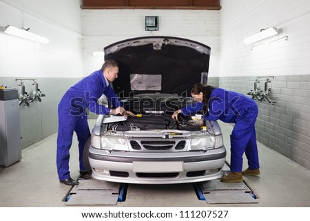 Mechanics looking at the engine in a garage - stock photo