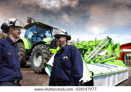 mechanics standing in a tractor yard, latest model of tractor and mower - stock photo