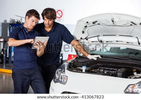 Mechanics Using Tablet Computer By Damaged Car - stock photo