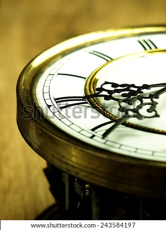 Mechanism of old clock on wooden background. Clock face and hands showing five minutes to midnight. - stock photo
