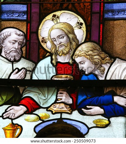 MECHELEN, BELGIUM - JANUARY 31, 2015: Stained Glass window depicting Jesus offering communion to His Apostles at the Last Supper, in the Cathedral of Saint Rumbold in Mechelen, Belgium. - stock photo