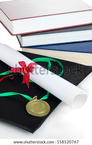 Medal for achievement in education with diploma, hat and books close up - stock photo
