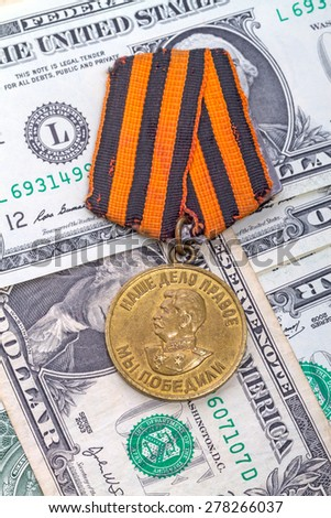 "Medal ""For Victory over Germany"" and dollars. The text on the medal ""Our cause is just - we won"" - stock photo"