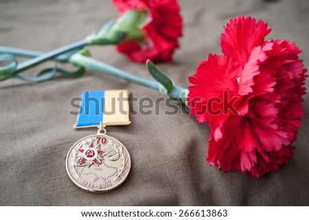 Medal 70 Years of Liberation of Ukraine from the Nazis and two red carnations. Still life dedicated to Victory Day. 9 May. - stock photo