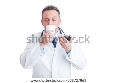 Medic or doctor smelling fresh coffee from disposable cup on his morning break - stock photo