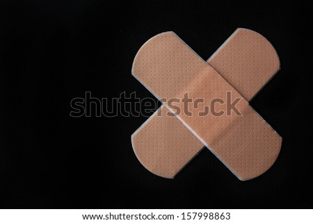 Medical adhesive bandage on black background - stock photo