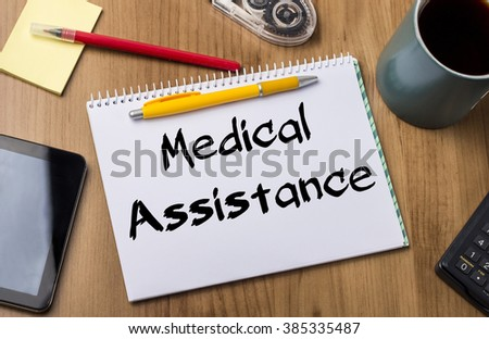Medical Assistance - Note Pad With Text On Wooden Table - with office  tools - stock photo