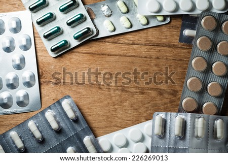 Medical background backdrop with frame border of pills tablets drugs on wooden table. Pharmacy. - stock photo