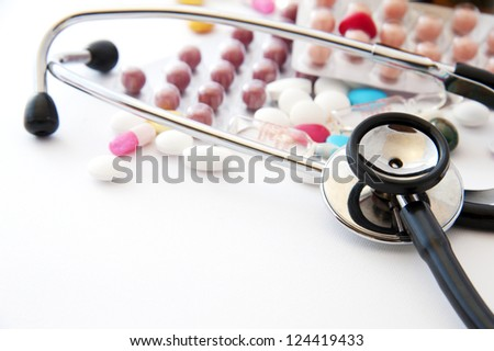 Medical background with pill, syringe, stethoscope, ampoules and bottles - stock photo