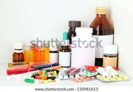 Medical bottles and pills on shelf - stock photo