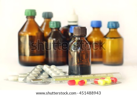 Medical bottles for mixtures, syrups and health-care oils with hypodermic and thermometer and pills on white background - stock photo
