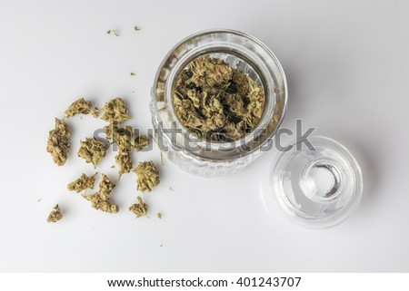 Medical cannabis buds in an open glass jar with marijuana flowers scattered aside and transparent lid on white background directly from above - stock photo