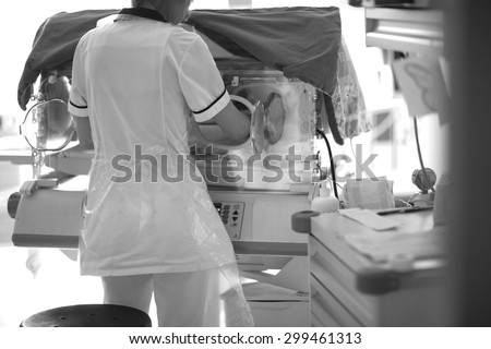 Medical checkup in neonatal intensive care unit; back of a doctor opening baby incubator - stock photo