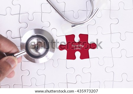 Medical Concept - A doctor holding a Stethoscope on missing puzzle with healthy care WORD - stock photo
