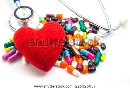 Medical concept : One red heart on Colorful  Pills  and doctors Stethoscope With white background for Cardiovascular disease or heart disease - stock photo