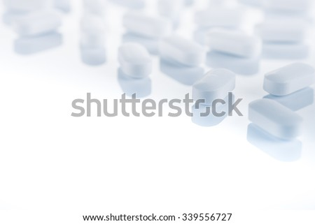 Medical concept or theme image with pills in the foreground. Product photo taken from above, low angle. Top view of medical pills on a glass, reflective table. Horizontal photo. - stock photo