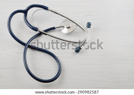 Medical concept, stethoscope on the white wooden table with room for text - stock photo