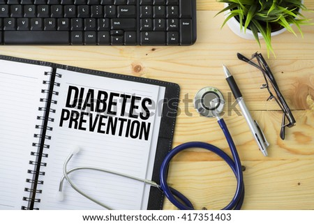 Medical Concept - Stethoscope with notebook written Diabetes Prevention with keyboard, green plant, a pen and spectacle on wooden background - stock photo