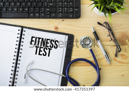 Medical Concept - Stethoscope with notebook written Fitness Test with keyboard, green plant, a pen and spectacle on wooden background - stock photo
