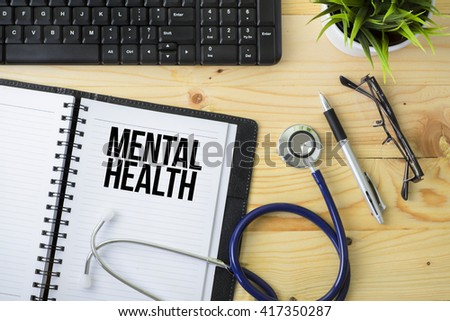 Medical Concept - Stethoscope with notebook written Mental Health with keyboard, green plant, a pen and spectacle on wooden background - stock photo