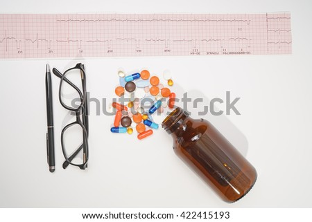 Medical doctor.Electrocardiogram Result ,glasses ,pen medicine and bottle isolated on white background. - stock photo